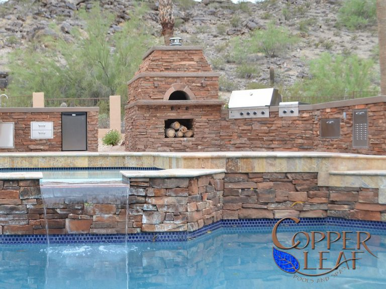Outdoor pizza oven built into an outdoor kitchen and featuring moss rock stone veneer.