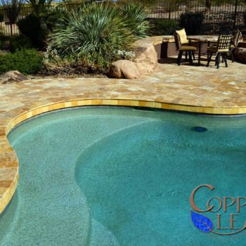Gold travertine pavers around a free form swimming pool.