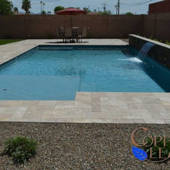 Geometric Pool - Large top step on a geometric pool with Aqua Blue Pebble Sheen with blue glass.