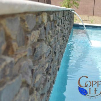 Sheer Descent Water Feature - Arizona schist natural stone veneer on raised wall.