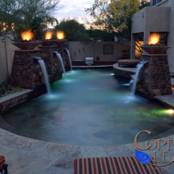 Geometric pool with flagstone step, scuppers in stone veneer columns and fire bowls in north Phoenix.