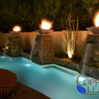 Resort style swimming pool with natural stone veneer columns with custom scuppers and fire bowls on top.