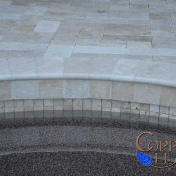 Travertine Coping - Travertine coping around edge of swimming pool with small travertine waterline tile and deck pavers.