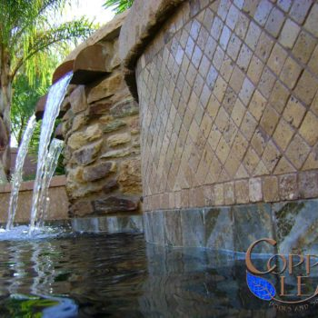 Copper scuppers on a water feature with natural stone and travertine tile.