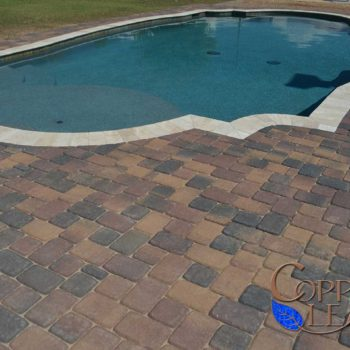 Grecian pool with travertine coping and Belgard Bella pavers.