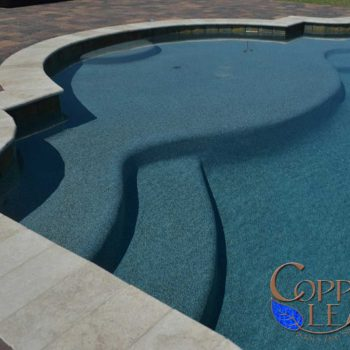 Large step on Grecian swimming pool finished with blue granite Pebble Sheen.