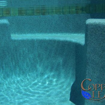 Underwater pool bench with blue granite Pebble Sheen finish and swim out steps.