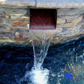 Resort style swimming pool with flagstone coping, stone veneer and featuring copper scuppers.