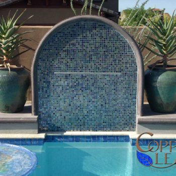 Custom built water feature with sheer descent waterfall, glass tile and architectural concrete.