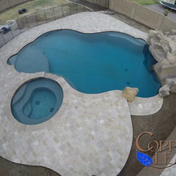 Overhead of a free form pool with rock slide and travertive pavers on the deck