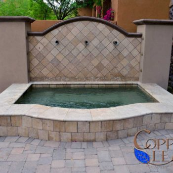 Raised Tuscan spa with travertine coping, architectural concrete and copper scuppers.