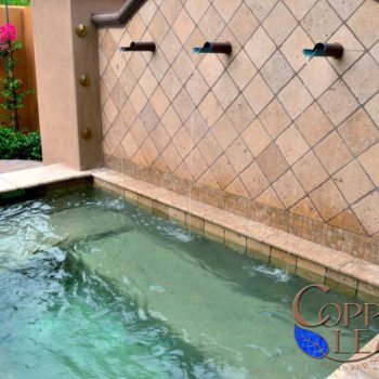 Custom spa disguised as a water feature with copper tube scuppers and travertine pavers.