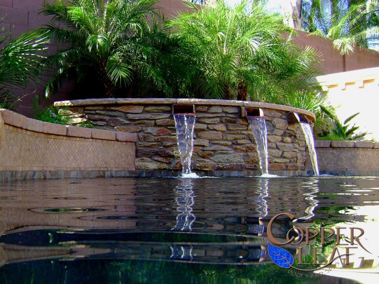 Custom water feature with copper scuppers featuring stone and paver accents.