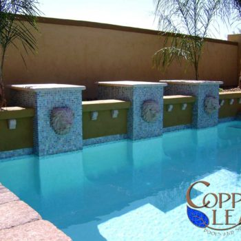 Geometric pool with glass tile columns, lion head scuppers and cantera accents.