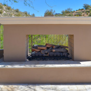 Double-sided outdoor fireplace with hearth