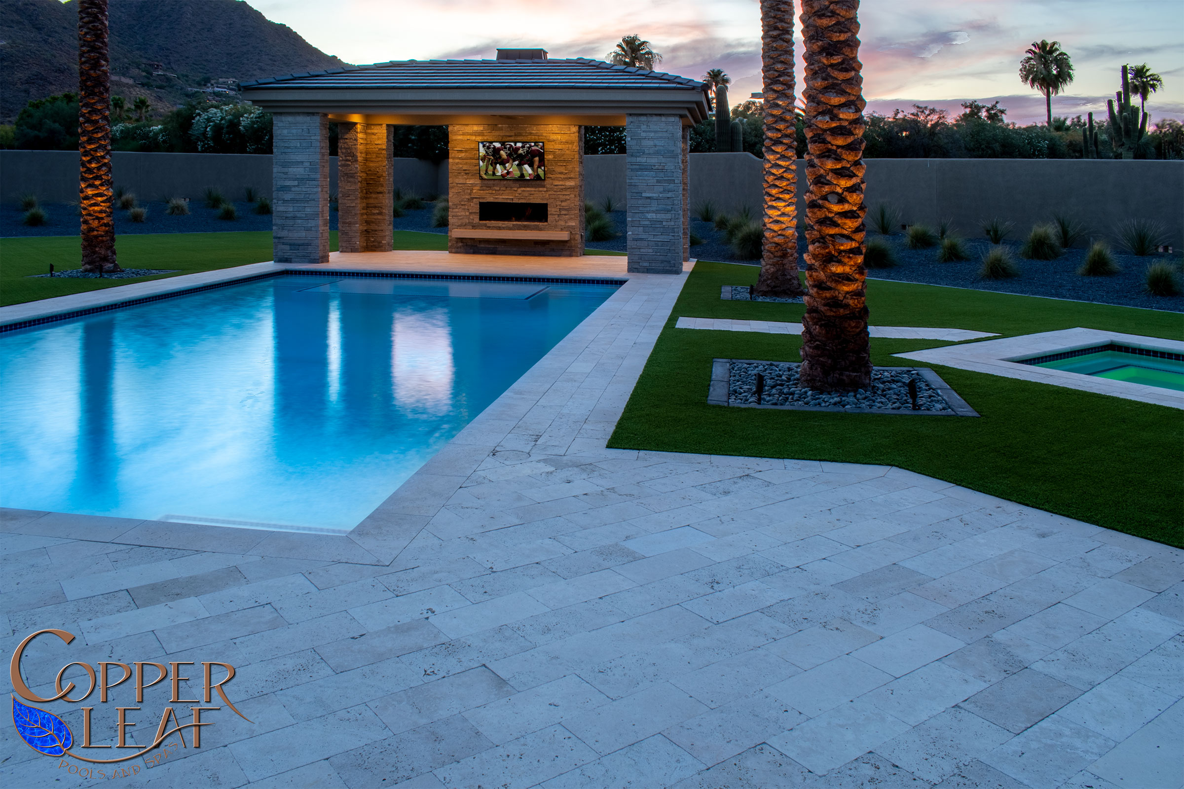 Synthetic grass surrounds the travertine pavers.