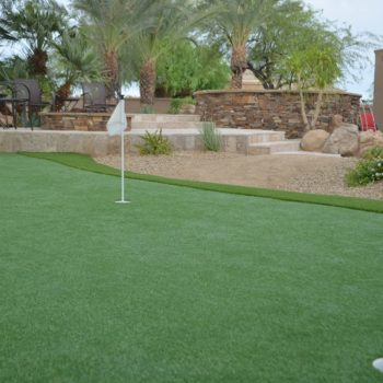 Putting green with built in fire pit in landscape.