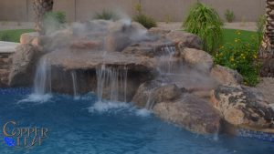Boulder waterfall on free form swimming pool