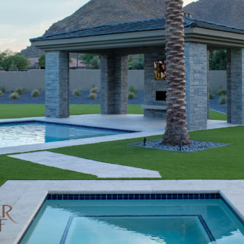 Square spa and rectangular pool, artificial turf and travertine coping
